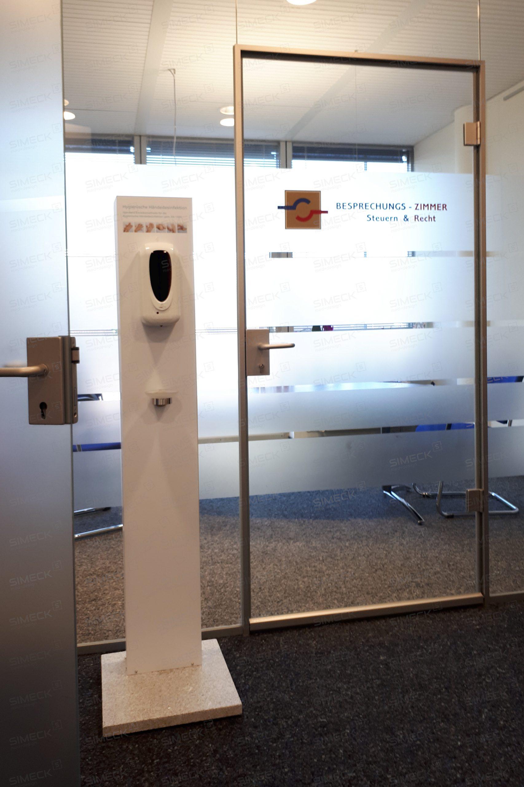 Desinfektionsständer unauffällig platziert in modernem Büroflur